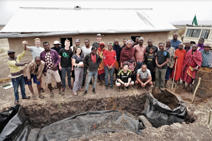 Students and community members stand next to biodigester